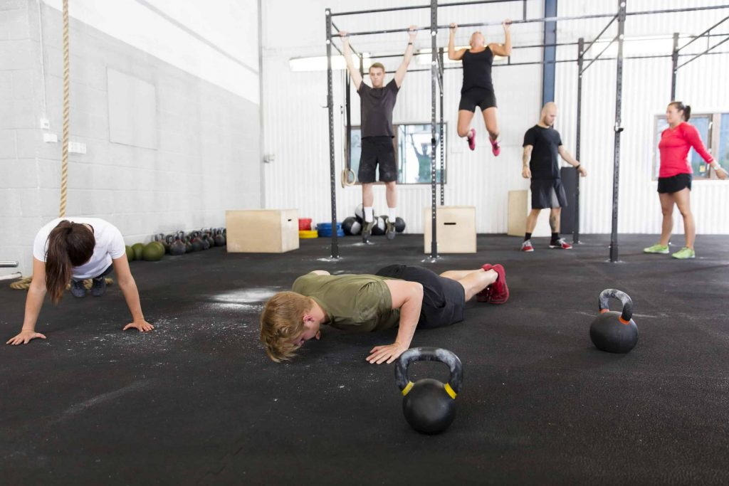Training push ups, hang ups and squat at a fitness gym center. Group workout.